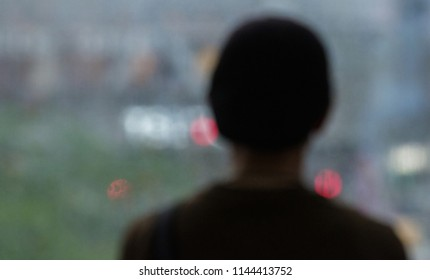Backview of a man standing looking outside a big glass window during rainy day.