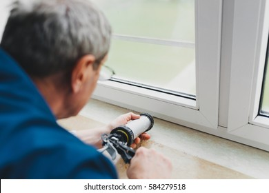 Backview of old man using a silicone tube for repairing the window indoor