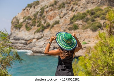 Backview portrait of a solo traveller female wearing green and blue hat looking at beautiful bay. Copy space.