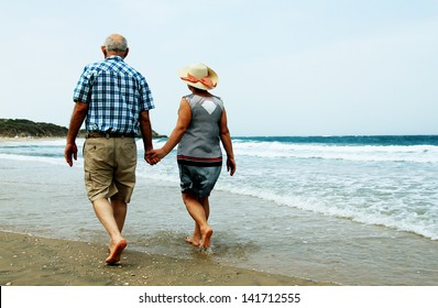 backview of senior couple walking on sandy beach