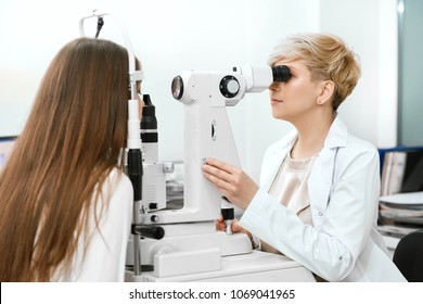 backview of skilled , expirienced assistant checking patient's vision, working in opthalmological laboratory. helping to save and improve eye health and vision. Wearing white uniform.