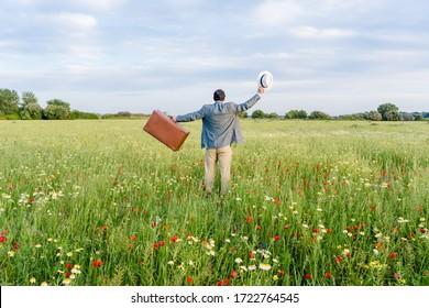 Rückblick auf unerkanntes Männchen am blauen Himmelstag im Freien Landschaftshintergrund. Person, die alten Koffer hält, entspannend Hoffnung Freiheit. Wegreisen oder Zurück-Szene, blühende Blumen