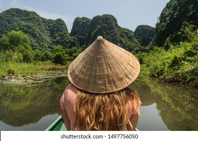Backwards blonde woman with vietnamese hat or  non la.  Tam Coc boat tour at Ninh Binh everyday riding tourists on Ngo Dong river in southeast asia. Vietnam,