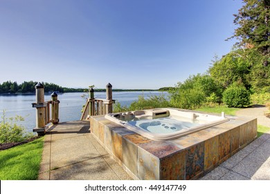 Backyard area with  awesome water view and hot tub with tile trim and concrete floor.