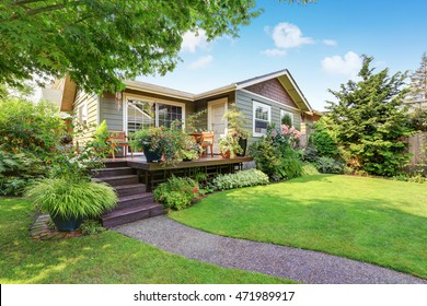 Backyard area with nicely trimmed garden. Wooden deck with stairs and flower pots. Northwest, USA