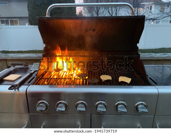 A backyard barbecue with cheeseburgers and hamburgers being charred. The stainless steel 6 burner grill has high flames and the meat is burning. There is a spatula and melting cheese near the flames.
