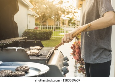 Backyard BBQ, person cooking steak, hamburger patties on a gas grill.