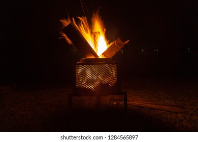 Backyard campfire in brazier against night sky with lights in the background - isolated, family fun in autumn or spring, holiday, sleepout and camping activity under supervision. Inspiration for relax