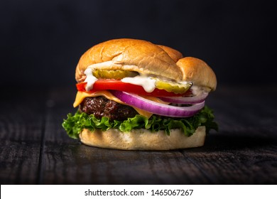 Backyard cheeseburger with American cheese, lettuce, tomato, red onion, pickles, and farmhouse bun on dark and moody wooden background