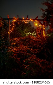 Backyard christmas illumination. Orange Christmas light string on a wooden pergola