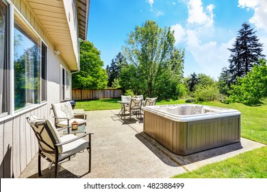 Backyard concrete floor patio area with hot tub. Well kept lawn around. Northwest, USA