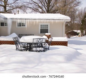 A backyard deck buried in snow after a blizzard.