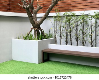 Backyard garden design with bench and cement fence