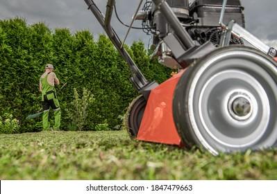 Backyard Garden Work with Lawn Aerator. Machine and Working Caucasian Gardener. Gardening Equipment.
