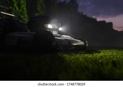 Backyard Grass Mowing During Late Summer Evening Hours. Modern Electric Grass Mower with LED Head Lights.