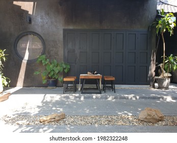backyard home decorate to relax area. black rouge sement wall and folding door. wood and steel table set. green plant on back.gray stone floor with step. small stone ground and two brown rocks