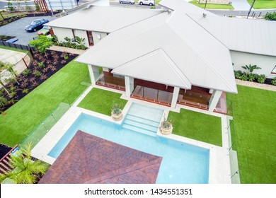 Backyard of the house with an attached pool and patio, covered with glass fencing on all sides and divided from the lawn area.