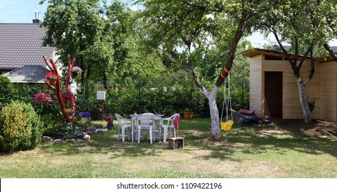 Backyard of an ordinary poor village house-- plastic furniture, a swing and an unfinished barn. Sunny summer day panoramic landscape