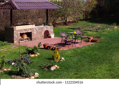Backyard Patio Area with Fireplace and Furniture. Green Party area. Barbecue Area. Stone.