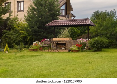 Backyard Patio Area with Fireplace and Furniture. Green Party area. Barbecue Area. Green grass.