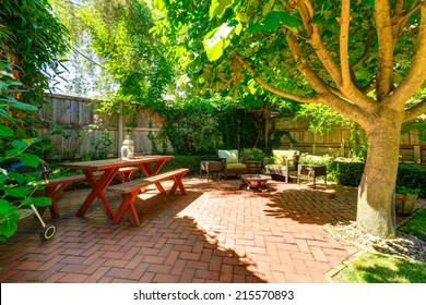 Backyard patio area with wooden table and benches, wicker chairs and fire pit
