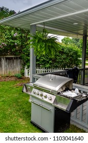 A backyard view of a barbeque with a Boston Fern  hanging in a covered porch with lilca bushes and wooden fence in the background.