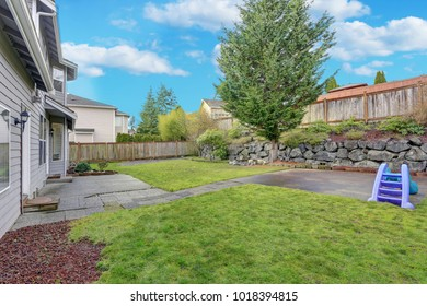 Backyard view with natural stone lanscape design and well kept lawn.