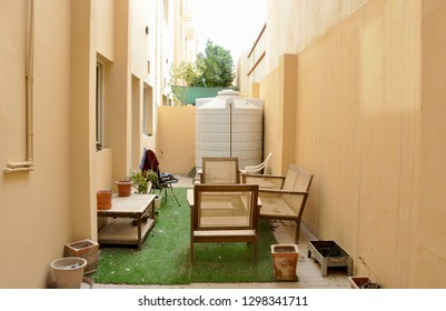 Backyard of a villa with old wooden furniture and water storage tank in background.