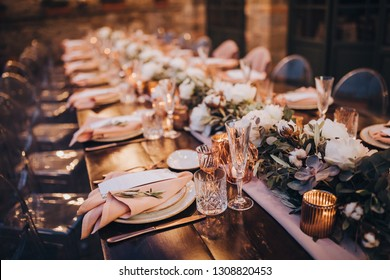 in backyard of villa in Tuscany there is banquet wooden table decorated with cotton and eucalyptus compositions, glasses, burning candles and plates are placed on table, evening