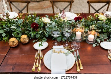 en el patio trasero de una villa en la Toscana, sobre una mesa de madera se sirven platos, tenedores, vasos y cuchillos decorados con flores