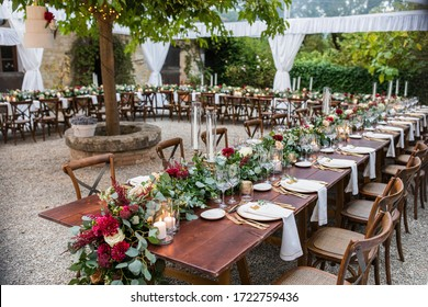 in backyard of villa in Tuscany there is a reception wooden table decorated with cotton and eucalyptus compositions, glasses, candles and plates are placed on table