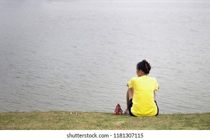 backyard of woman sitting on green grass with pond in background. Lonelyness concept