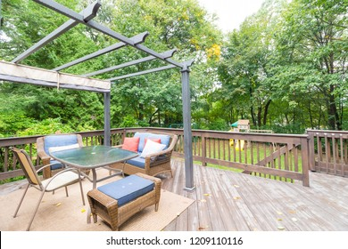 Backyard wooden deck with chairs railing and view of backyard with green trees