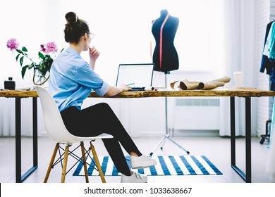 Bacl view of charming female entrepreneur sitting at desktop with garment equipments and analyzing information from laptop computer with blank screen for your fashion advertising connected to wifi