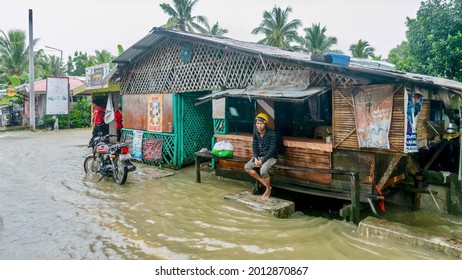 Baco, Oriental Mindoro, Philippines - July 23, 2021. Heavy monsoon rains flood a local restaurant along the National Highway, where a Filipino man sits on a bench in the rain.