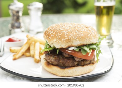 Bacon and Bleu Stuffed Cheeseburger topped with arugula tomato on a toatsed sesame seed bun served with fries ketchup and beer