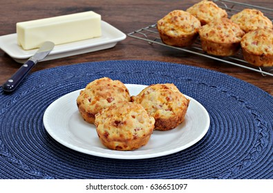 Bacon and cheddar cheese muffins on a plate with more cooling in background.