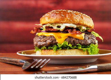 Bacon cheese burger on plate with homemade brioche bun  , red wooden log background