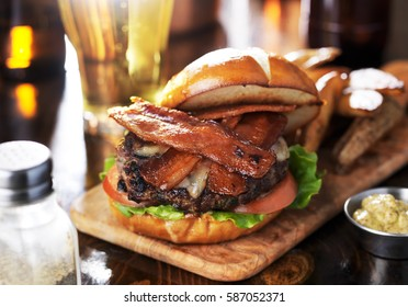 bacon cheeseburger on toasted pretzel bun served with fries and beer shot with selective focus