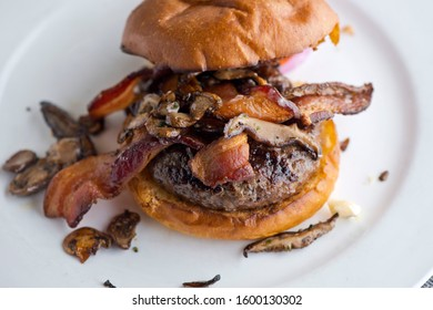 Bacon Cheeseburger with swiss cheese. Traditional classic american restaurant and pub menu item. Cheese burger served with melted swiss cheese crispy bacon and sauteed mushrooms.