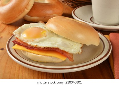 A bacon egg and cheese sandwich on a bagel with coffee in the background