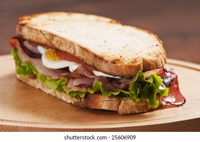 bacon and egg sandwich on wooden board