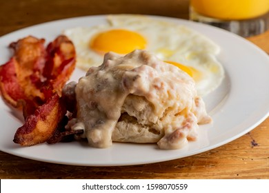 Bacon, Eggs and biscuits. Traditional classical American diner or French Bistro brunch item favorite. Biscuits and White Gravy. Homemade white sausage gravy served with fried eggs and crispy bacon.