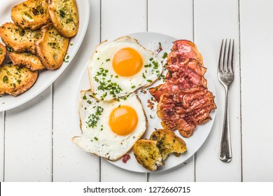 bacon and eggs for breakfast with chives and bread, top view,