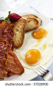 Bacon and eggs, with toasted croutons and strawberries.  A delicious breakfast.