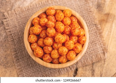 Bacon flavored corn puff balls in wooden bowl on burlap napkin. Cinema snacks. Copy space