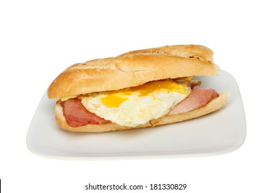 Bacon and fried egg in a baguette bread roll on a plate isolated against white