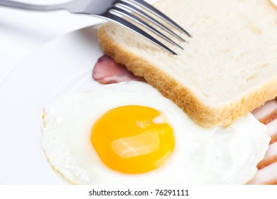 bacon with  fried  eggs on a plate, fork and bread isolated on white