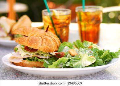 Bacon, lettuce, tomato, turkey and avocado sandwich on a croissant at an outdoor cafe