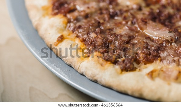 Bacon meat pizza cooked on a blue dish on a wooden table